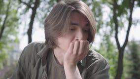 Portret van een eenzame gedeprimeerde droevige jonge mens met het doordringen in zijn neuszitting in het park De kerel is zenuwac stock video