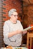 Portret van een elegante bejaarde dame die zich bij de vakantielijst bevinden stock fotografie