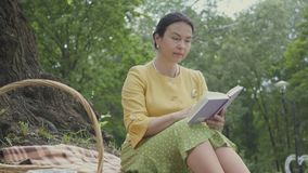 Portret van een elegante mooie rijpe vrouw die de boekzitting op de deken lezen onder de boom in het park rijs stock videobeelden