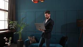 Portret van een elegante zakenman met laptop bij het binnenland van het luxe blauwe bureau stock videobeelden