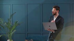 Portret van een elegante zakenman met laptop bij het binnenland van het luxe blauwe bureau stock video
