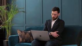 Portret van een elegante zakenmanzitting met laptop op de laag bij het binnenland van het luxe blauwe bureau stock videobeelden