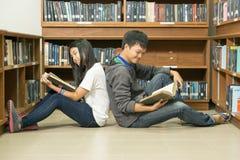 Portret van een ernstige jonge student die een boek in een bibliotheek lezen stock afbeeldingen