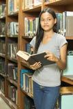 Portret van een ernstige jonge student die een boek in een bibliotheek lezen royalty-vrije stock afbeeldingen