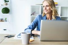 Portret van een ernstige onderneemster die laptop in bureau met behulp van royalty-vrije stock fotografie