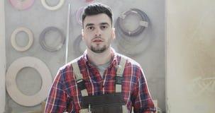 Portret van een ernstige timmerman in een bouw globaal in een meubilairfabriek stock footage