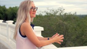 Portret van een Europees leuk blonde de afstand onderzoeken, een jonge gelukkige vrouw of een vrolijk meisje die van aard geniete stock video