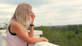 Portret van een Europees leuk blonde de afstand onderzoeken, een jonge gelukkige vrouw of een vrolijk meisje die van aard geniete stock footage