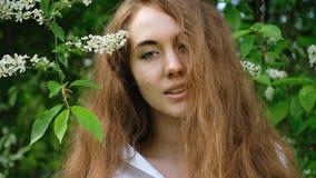 Portret van een Europees meisje met lang stromend haar in aard, langzame motie Mooie leuke jonge en vrouw die stellen kijken stock footage