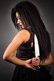 Portret van een expressieve jonge vrouw die een groot mes houden aan haar Stock Foto