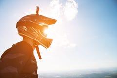 Portret van een fietser in een volledig-gezichtshelm en zonnebril tegen een achtergrond van een berg royalty-vrije stock fotografie
