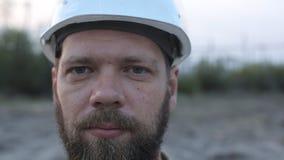 Portret van een gebaarde mens in een witte helm stock footage