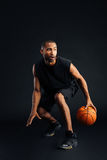 Portret van een geconcentreerde Afrikaanse sportenmens die in basketbal speelt Royalty-vrije Stock Foto's