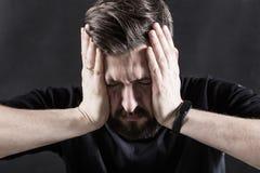 Portret van een gedeprimeerde mens met een nadenkende stokvoering zijn hoofd en het behandelen van zijn gezicht met zijn handen o stock afbeeldingen