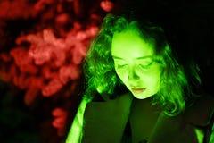 Portret van een geheimzinnige vrouw in groene verlichting met koraalachtergrond stock foto