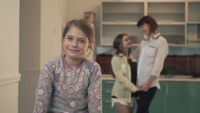 Portret van een gelukkig glimlachend meisje op de achtergrond van twee die oudere zusters omhelzen Familieverhoudingen stock videobeelden