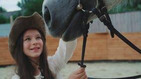 Portret van een gelukkig meisje die bij haar vriendschappelijk wit paard op het gebied glimlachen 4K stock footage