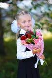 Portret van een gelukkig schoolmeisje in een uniform met boeket van bloemen Stock Afbeeldingen