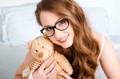 Portret van een gelukkig, vrolijk, jong blondemeisje met glazen, s Stock Foto's