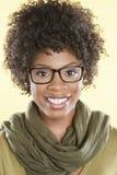 Portret van een gelukkige Afrikaanse Amerikaanse vrouw die glazen met stole om haar hals over gekleurde achtergrond dragen Stock Foto