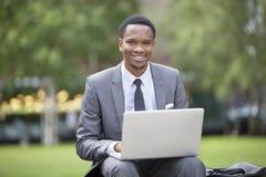 Portret van een gelukkige Afrikaanse Amerikaanse zakenman die laptop in park met behulp van Royalty-vrije Stock Foto