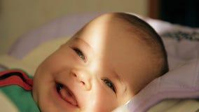 Portret van een gelukkige baby die in een een wieg en het glimlachen close-up liggen stock videobeelden