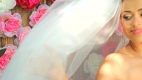 Portret van een gelukkige bruid Een mooie bruid in een sluier houdt een boeket van bloemen tegen de achtergrond van a stock footage