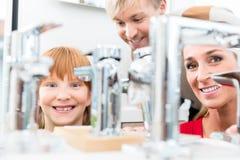 Portret van een gelukkige familie die een nieuwe tapkraan van de badkamersgootsteen zoeken stock afbeeldingen