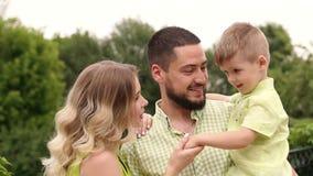 Portret van een gelukkige familie met een kleine zoon in het Park in de zomer, langzame mo stock videobeelden