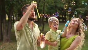 Portret van een gelukkige familie met een kleine zoon in een Park met zeepbels Langzame mo stock videobeelden