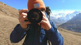 Portret van een gelukkige gebaarde reizigersfotograaf in zonnebril en een hoed met een reflexcamera in zijn handen en het nemen stock video