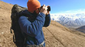 Portret van een gelukkige gebaarde reizigersfotograaf in zonnebril en een hoed met een reflexcamera in zijn handen en het nemen stock videobeelden