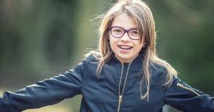 Portret van een gelukkige glimlachende tiener met tandsteunen en glazen royalty-vrije stock foto's