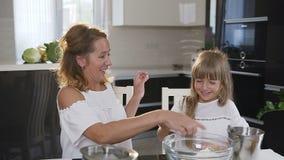 Portret van een gelukkige jonge familiekoks in de keuken De vrouw met haar meisje bereidde een deeg voor baksel voor en stock video