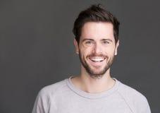 Portret van een gelukkige jonge mens die op grijze achtergrond glimlachen Royalty-vrije Stock Afbeeldingen