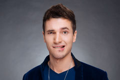 Portret van een gelukkige jonge mens die op grijze achtergrond glimlachen Royalty-vrije Stock Afbeelding