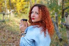 Portret van een gelukkige jonge mooie vrouw met rood haar en het onderzoeken van de camera royalty-vrije stock afbeelding