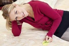 Portret van een gelukkige jonge vrouw die op matras met prijskaartje doen leunen Royalty-vrije Stock Afbeeldingen