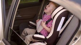 Portret van een gelukkige lachende jongen in een autozetel in de auto stock videobeelden