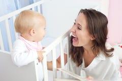 Portret van een gelukkige moeder die met leuke baby in voederbak lachen stock afbeelding
