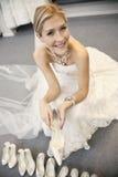 Portret van een gelukkige mooie vrouw in de zitting van de huwelijkskleding met schoeisel in bruids opslag Stock Afbeeldingen