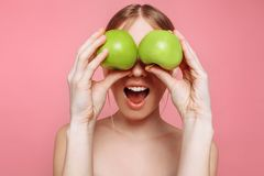 Portret van een gelukkige mooie vrouw die een appel, op een roze achtergrond houden royalty-vrije stock afbeeldingen