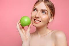 Portret van een gelukkige mooie vrouw die een appel, op een roze achtergrond houden stock fotografie