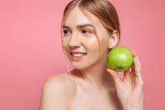 Portret van een gelukkige mooie vrouw die een appel, op een roze achtergrond houden royalty-vrije stock afbeelding