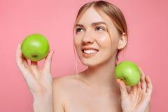 Portret van een gelukkige mooie vrouw die een appel, op een roze achtergrond houden stock foto