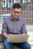 Portret van een gelukkige student die aan laptop in openlucht werken Stock Foto's