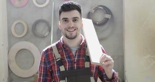 Portret van een gelukkige timmerman die een houten raad op zijn schouder houden stock video