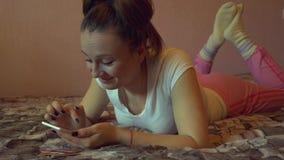 Portret van een gelukkige vrouw in haar het mooie slaapkamer texting stock video