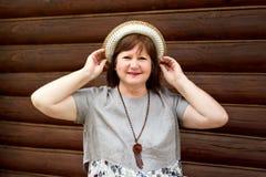 Portret van een gelukkige vrouw op middelbare leeftijd bbw in een hoed en linnenkleding dichtbij een logboekmuur stock afbeeldingen