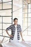 Portret van een gelukkige vrouwelijke contractant met handen op heupen bij bouwwerf royalty-vrije stock foto